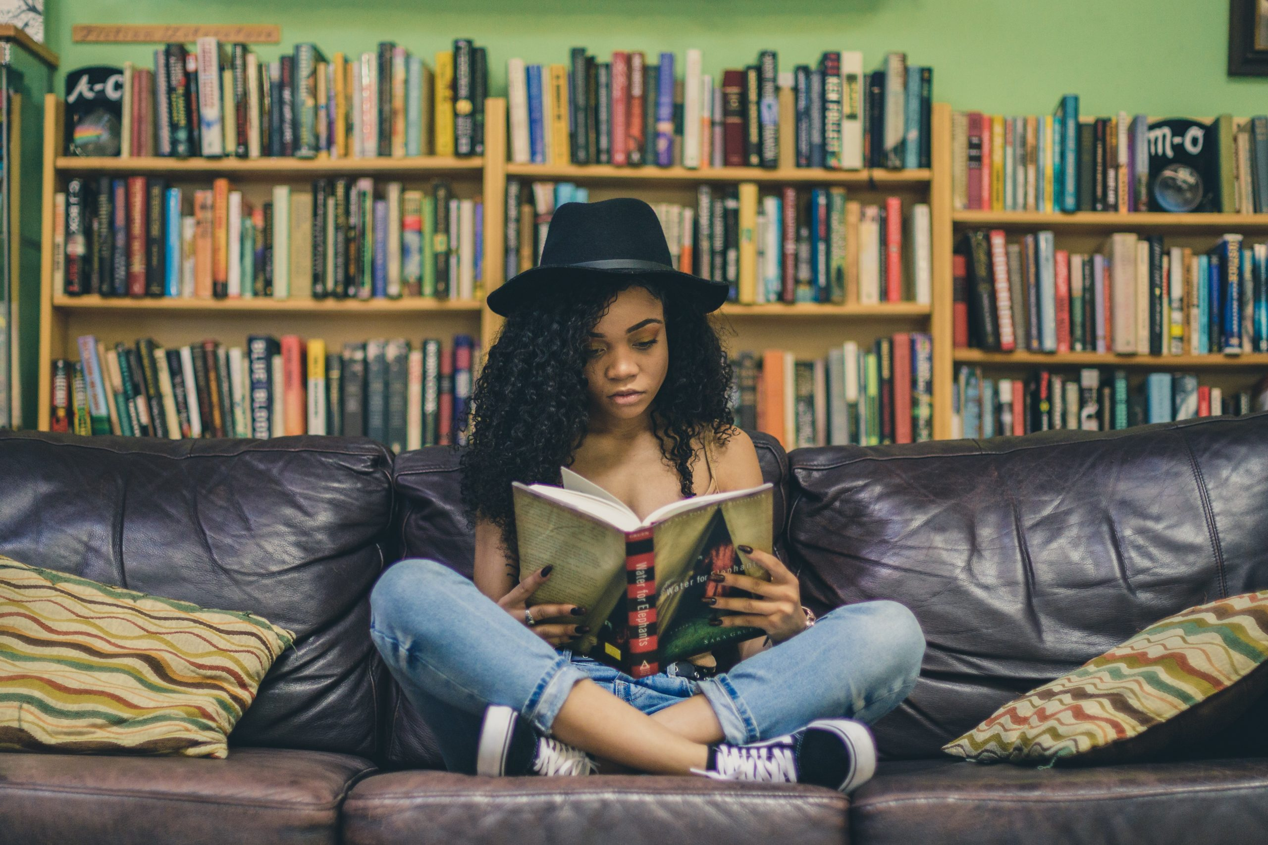 girl on a sofa reading in a library