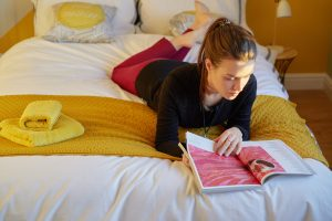 reading a magazine in bed in a B-Hive Living coliving home